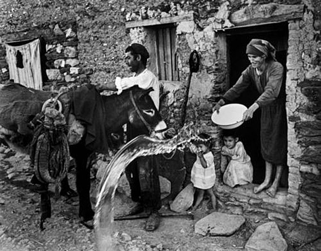 "W. Eugene Smith - A farmer unloads his donkey in front of his home. His wife throws out the dirty dishwater. Extremadura. SPAIN. 1951. / From ""Spanish Village"" photo-essay."