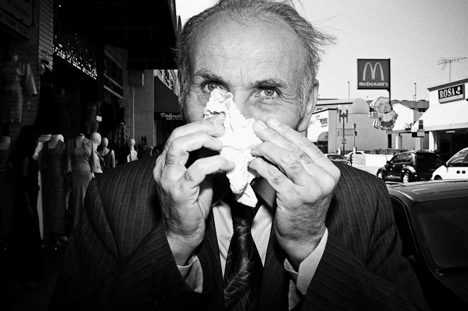 I was shooting in Downtown LA, and saw this guy walking down the street--blowing his nose. I then approached him, about to take a photo-- and he put down the tissue. I then told him it was okay, and to continue blowing his nose. He then laughed, and started blowing his nose again. I took two shots, and this one was the more interesting one. I think it looks quite candid, even though it was posed.