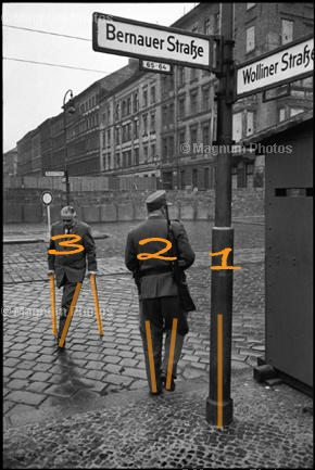 HCB plays a 1,2,3 rhythm of the lamp post, the soldier and the man on his crutches. WEST GERMANY. 1962. West Berlin. The construction of the Berlin Wall. © Henri Cartier-Bresson