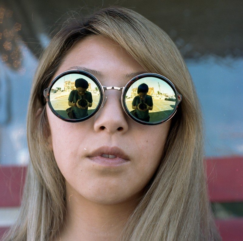 Portrait of my sister in Los Angeles, 2014. Shot on a Hasselblad 501c on Kodak Portra 400. Note my reflection In her glasses.