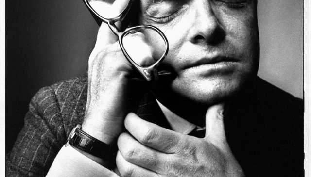 Close-up of writer Truman Capote, eyes closed, holding a pointed finger to his temple