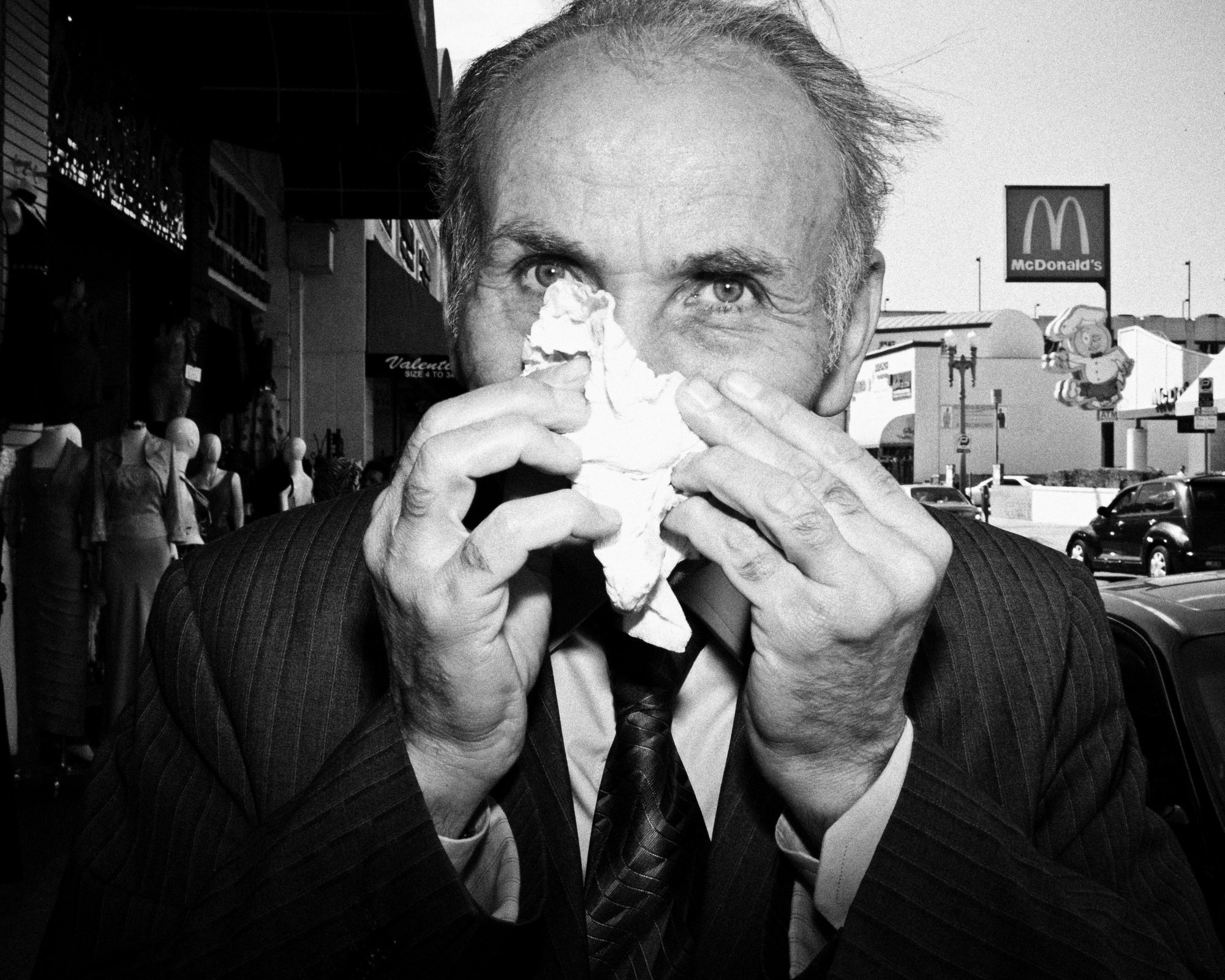 Downtown LA, 2012. Man blowing nose with tissue. Shot with Leica M9, flash, 35mm at 1 meters.