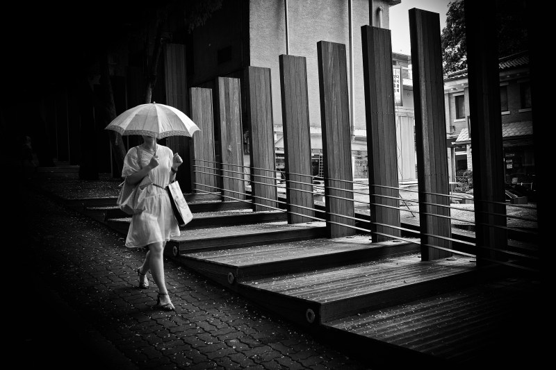 Diagonal leading line of woman and umbrella. Seoul, 2009