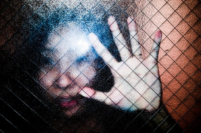 Cindy and hand through criss-cross diamond-patterned, translucent glass window. Tokyo, 2017
