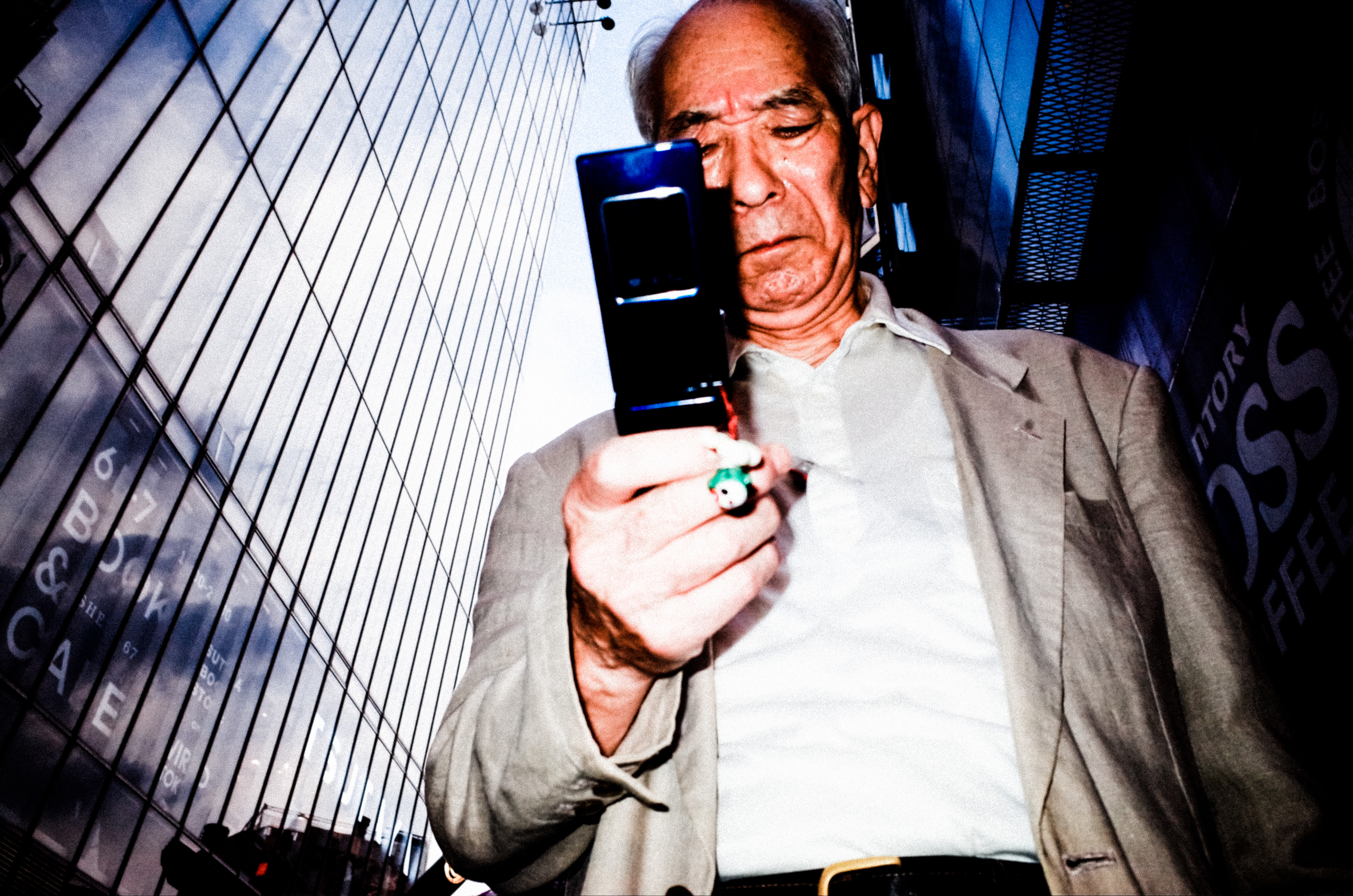 Low angle shot of man with flip phone. Shot with flash. Tokyo, 2017