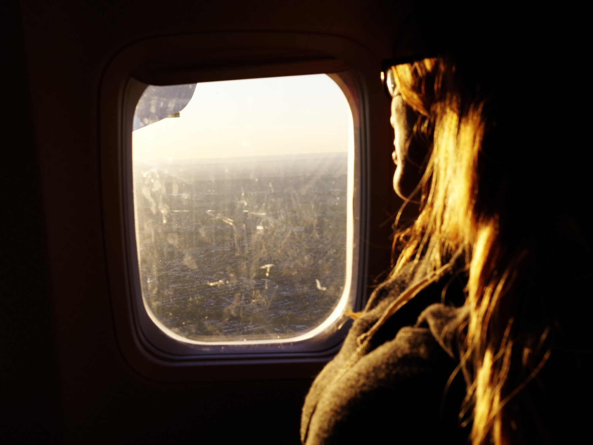 Woman in airplane. Sunset over NYC. Pentax 645Z
