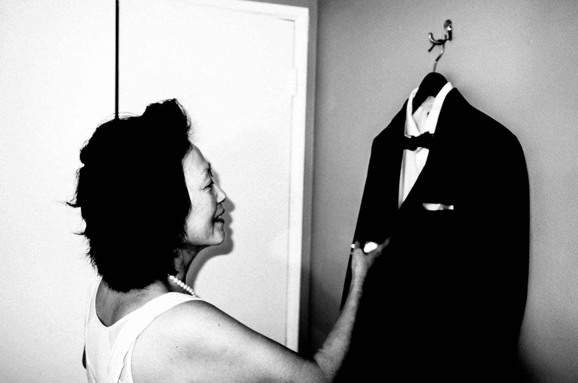 Mom holding my suit jacket. Day of my wedding, 2016