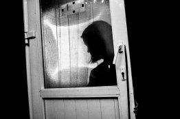 Silhouette of woman behind door. Hanoi, 2017