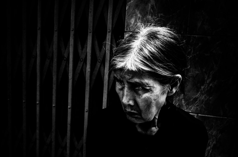 Dramatic picture of Hanoi woman. Background darkened, and her face and eyes brightened for dramatic effect.