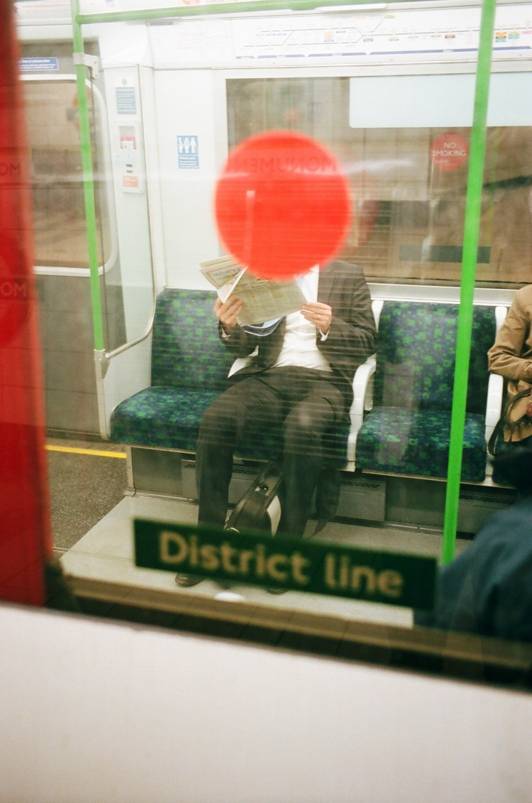 Red dot overlapped with man in suit. London tube, by Eric Kim