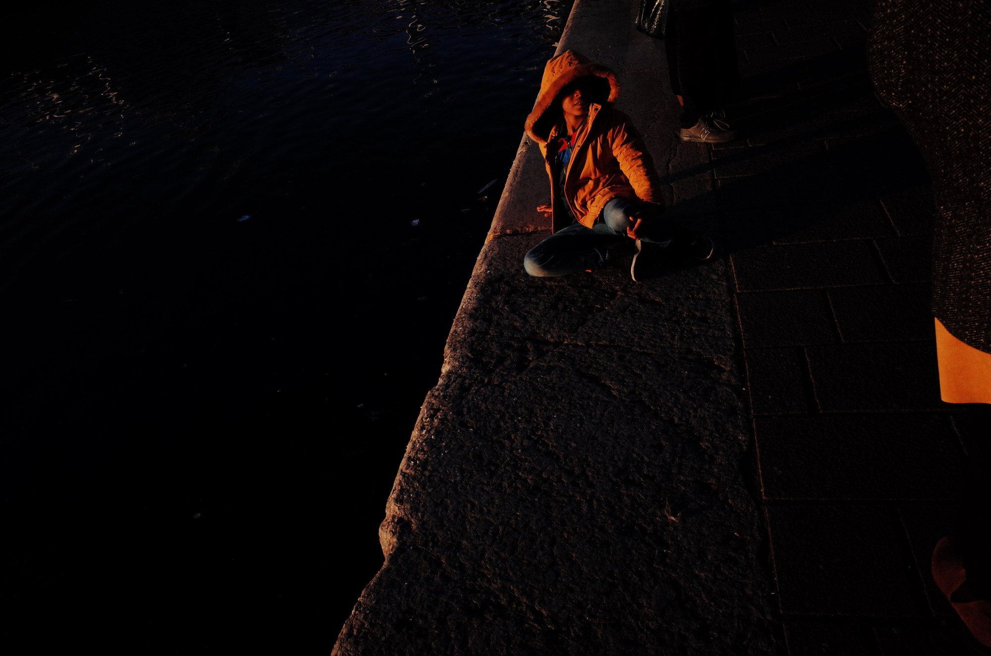 Golden hour, boy in orange jacket by water. Marseille, 2017