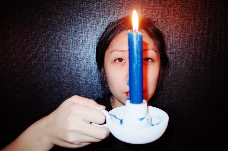 Cindy with blue candle over face. Marseille, 2017