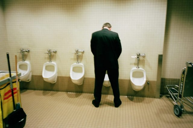 Suit and urinal. Bathroom.
