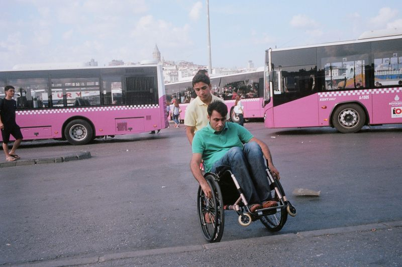 Man in green shirt in wheelchair, and pink buses. Istanbul, 2013