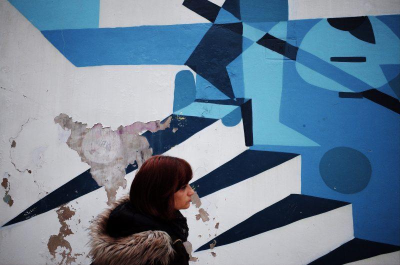 Graffiti wall and walking woman. Lisbon, 2018