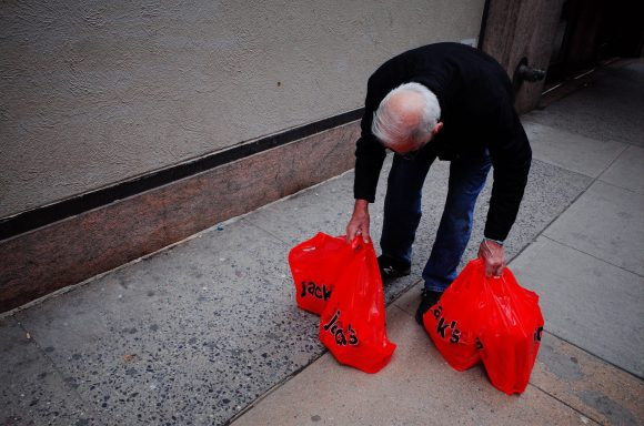 man bending over, picking up two red bags, new york city