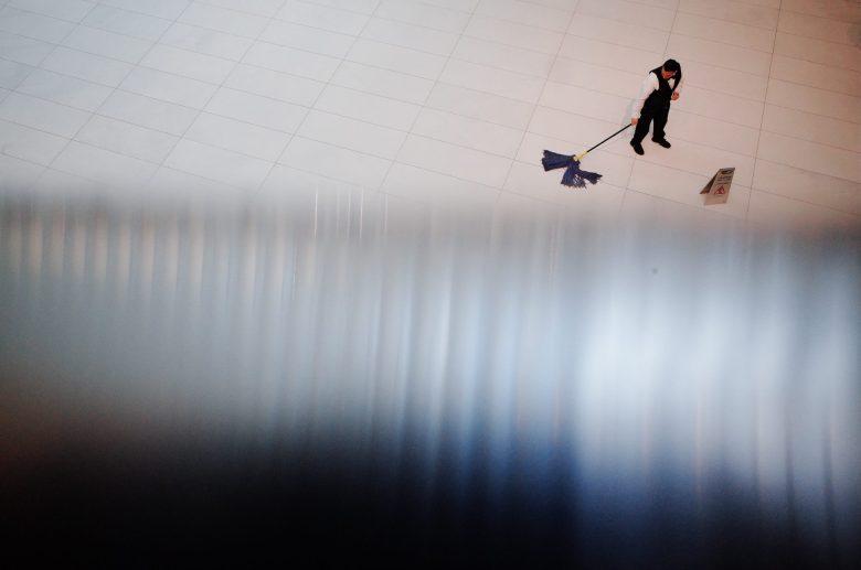 Depth, high angle. Man mopping floors. NYC, 2018