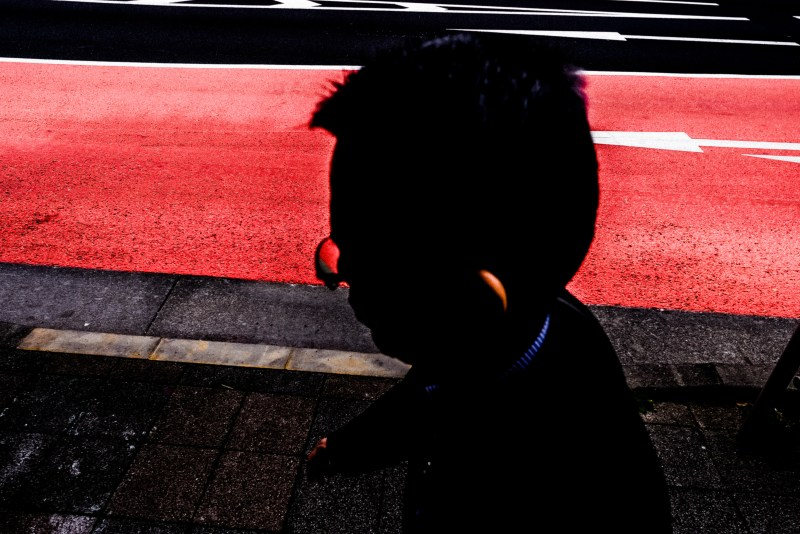 High angle perspective photo. Man with glasses silhouette, with red background. Tokyo, 2018