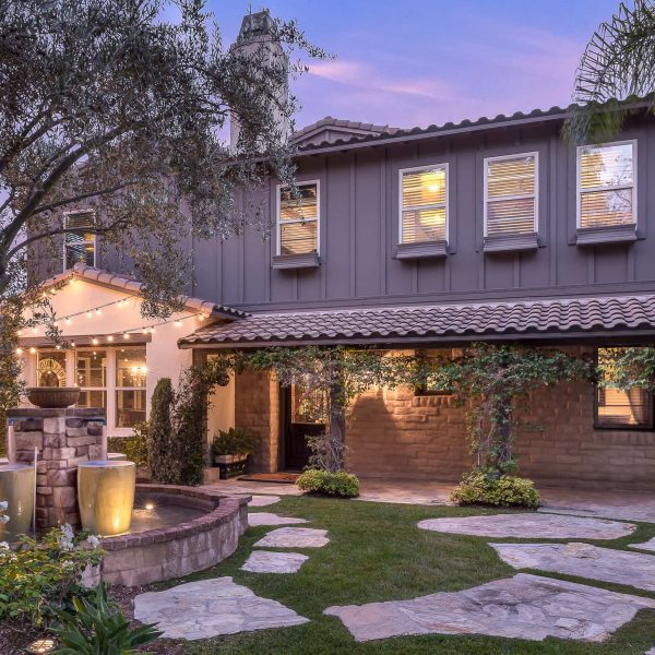 Orange County Luxury Real Estate Photography featuring a Ladera Ranch home at twilight with majestic purple hues and glowing orange lights and trees on the left and right of the image framing the home