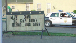 cop behind sign pic