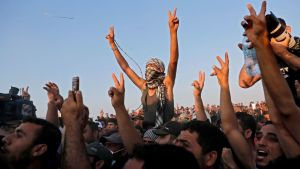 Supporters of Hamas leader Ismail Haniyeh react during his speech near the border with Israel east of Gaza City on May 15