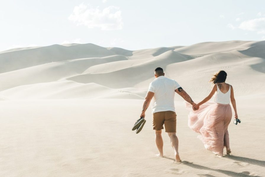 engaged couple walking in sand