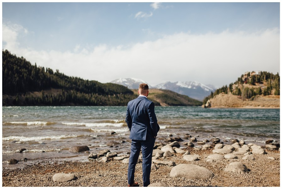 Groom waiting for first look at Dillon Reservoir in Dillon, Colorado.