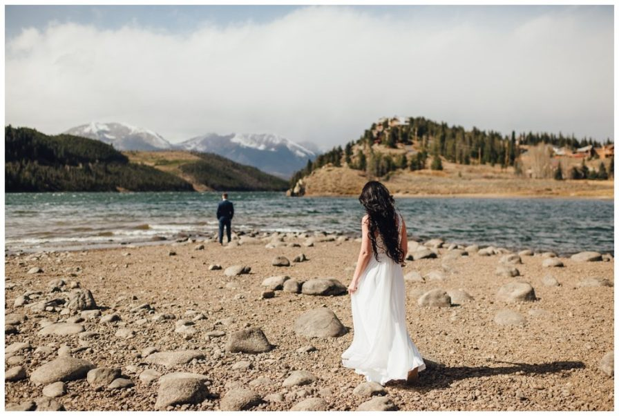 Bride walking to groom for their first look beside the water.