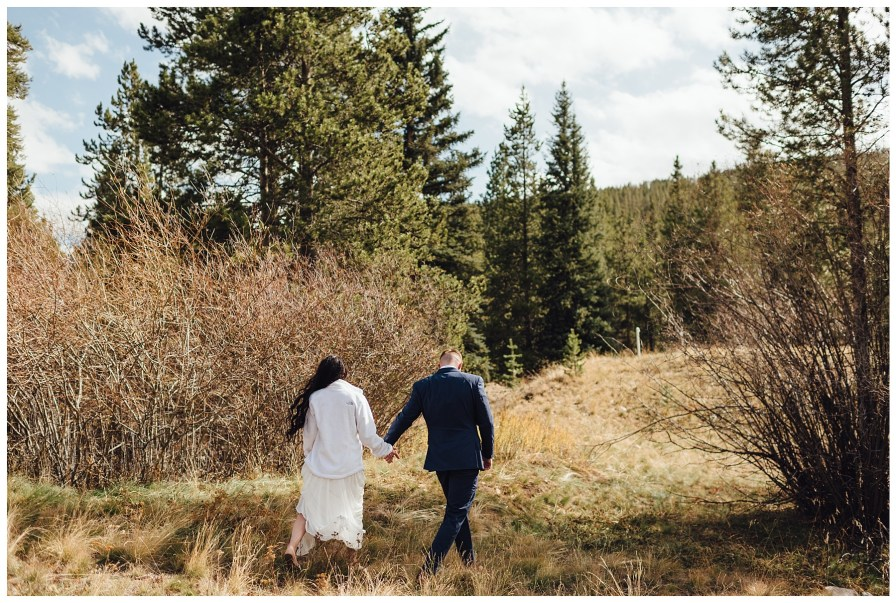 Bride and groom walking in the mountains on their wedding day.