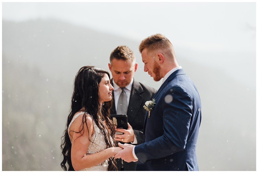 Groom says his vows to his bride while the snow lightly falls