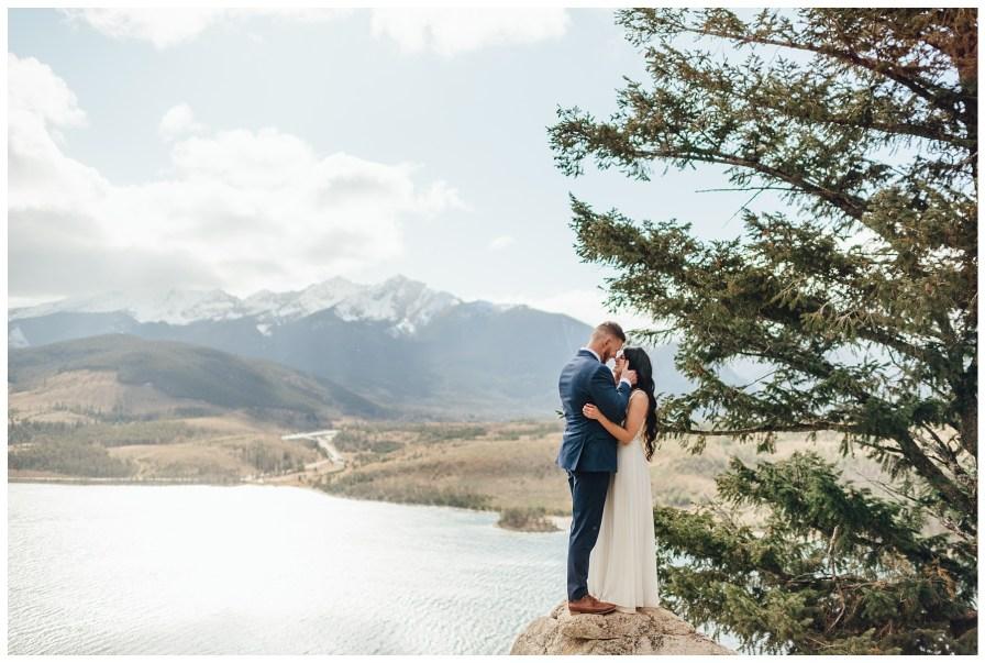Adventurous bride and groom crawl up the rocks for romantic photos