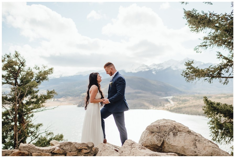 Bride and groom stand atop the rocks at Sapphire Point