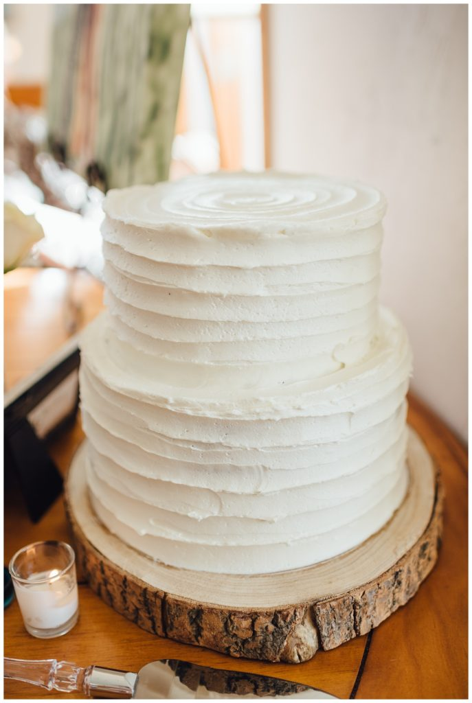 Simple white wedding cake on wooden tree stand