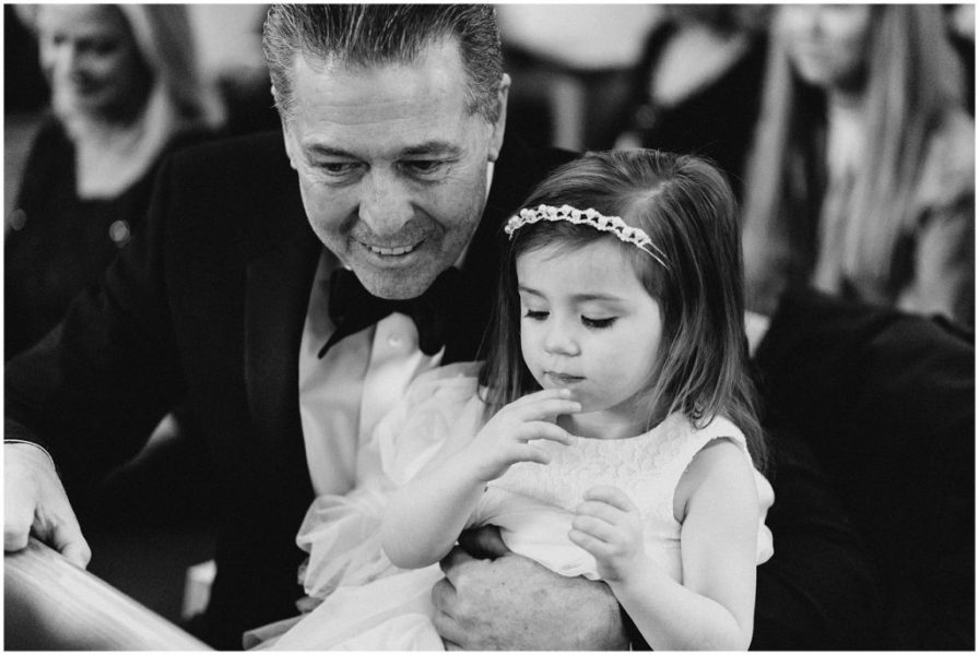 Grandfather sharing a moment with his granddaughter at a wedding