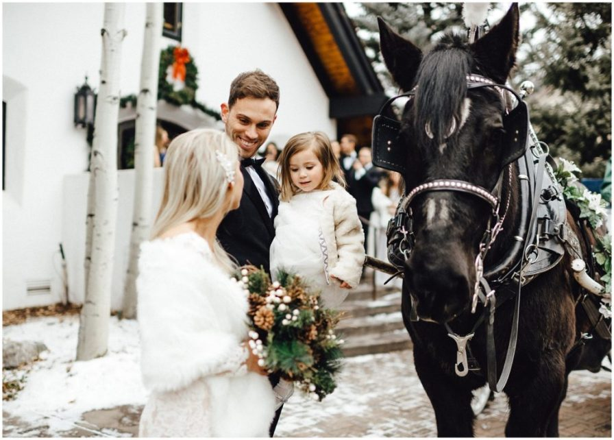Bride and groom getting ready for their carriage ride after their snowy winter elopement in Vail Colorado