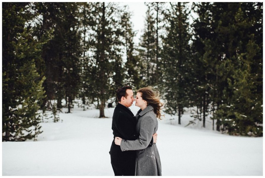 Couple embraces each other amidst evergreen trees