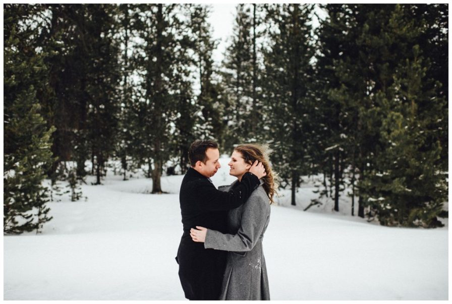 He goes in for a kiss amidst the evergreen trees