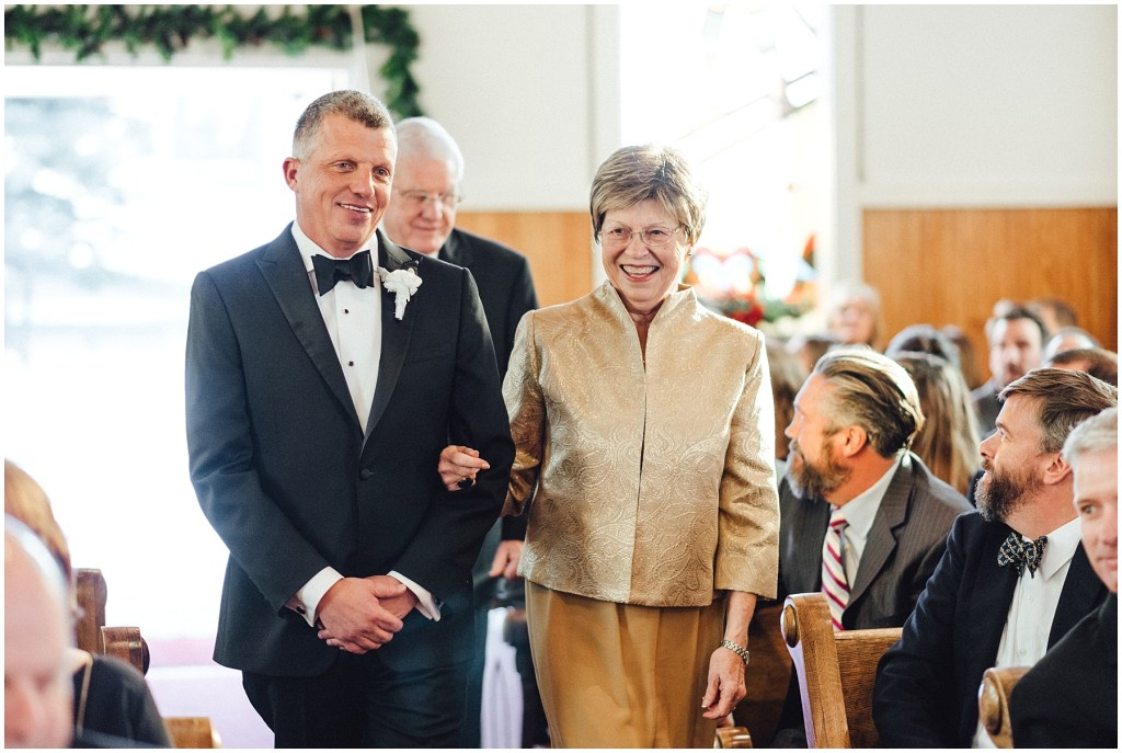 Groom walking down the aisle with his mom