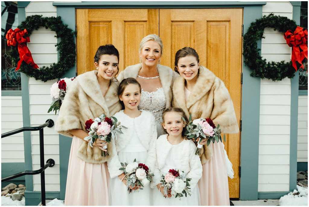 The bride with her bridal party in front of Father Dyer United Methodist Church , all cozy for this Breckenridge winter wedding.