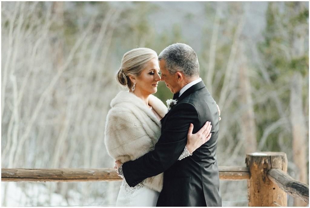 Romantic bride and groom embracing at Breckenridge winter wedding.