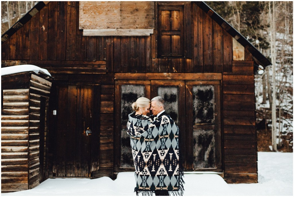 Couple getting cozy with a blanket in front of the cabin at their Breckenridge winter wedding.