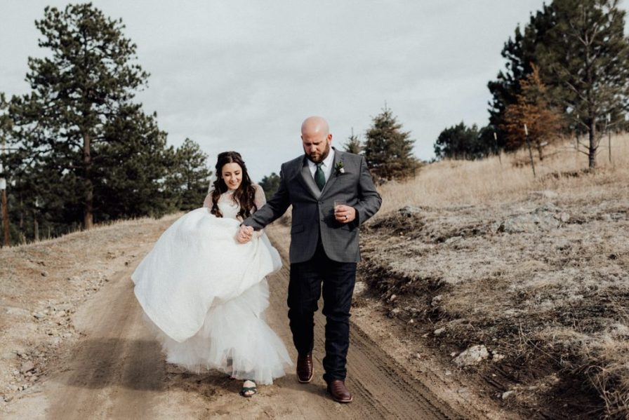 bride and groom walk down trail in Evergreen, Colorado