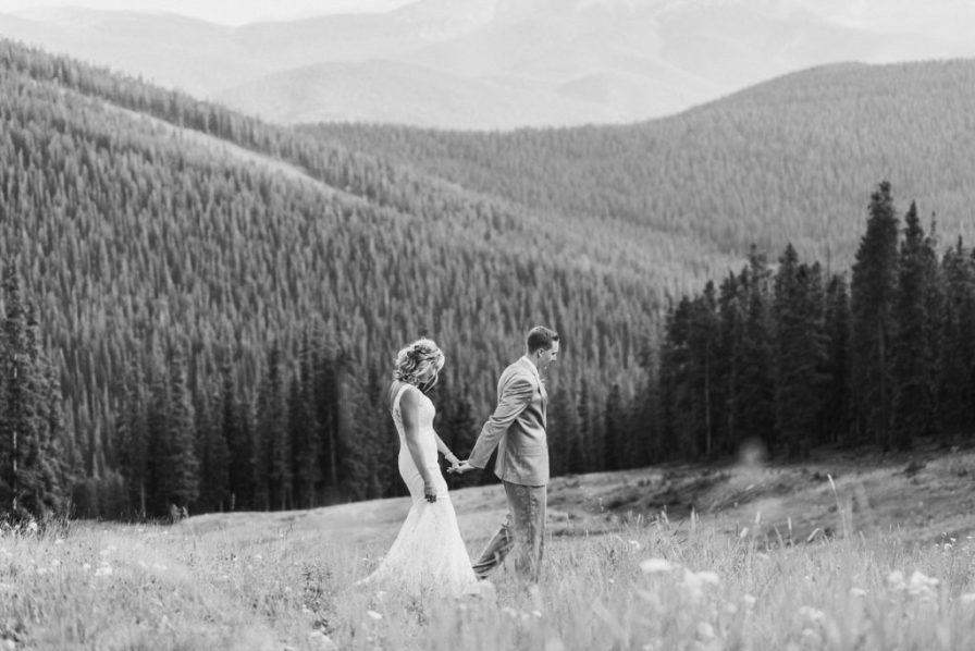Bride and groom walk through meadow in Keystone