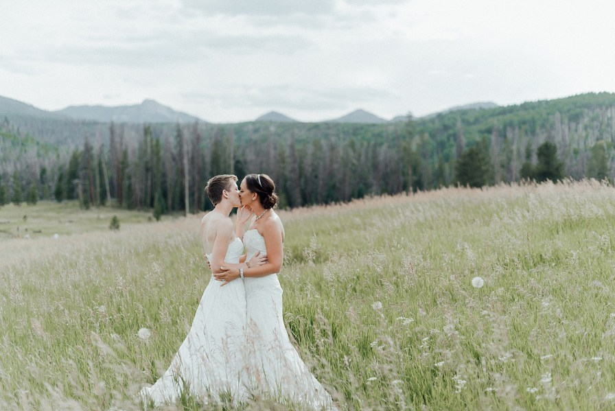 Brides embrace each other in the grassy field of this Midnight Ranch wedding