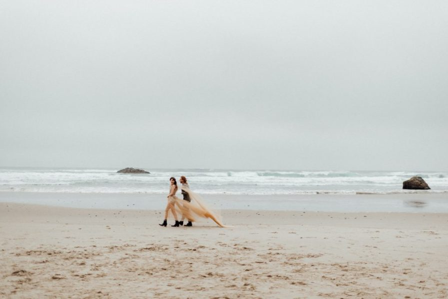Couple walks along beach in this Oregon coast elopement
