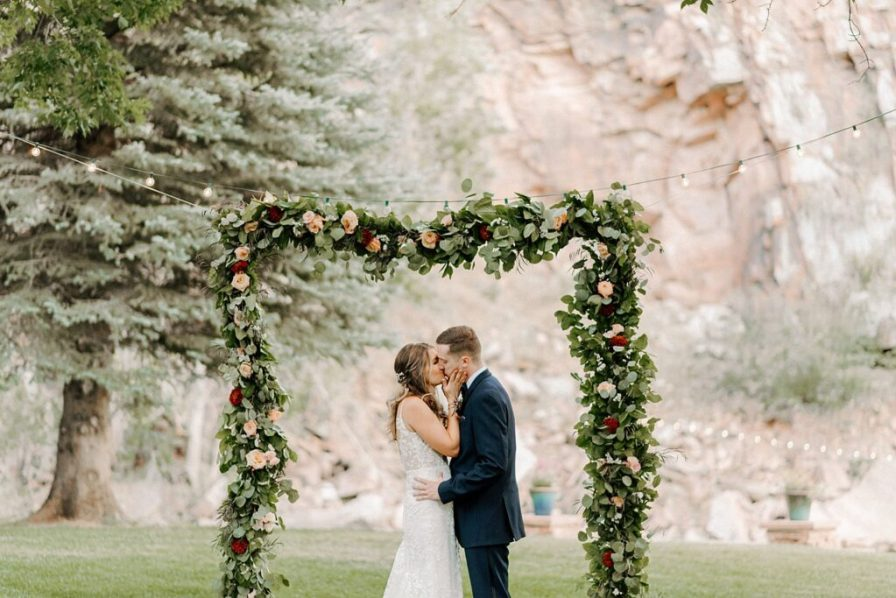 bride and groom kiss under flower arch at River Bend