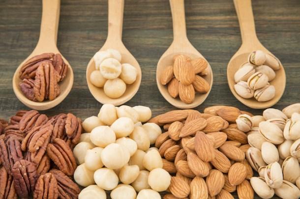 Group of nuts on wooden table. Almonds, pistachios, macadamia and pecan nut erikasglutenfreekitchen.com
