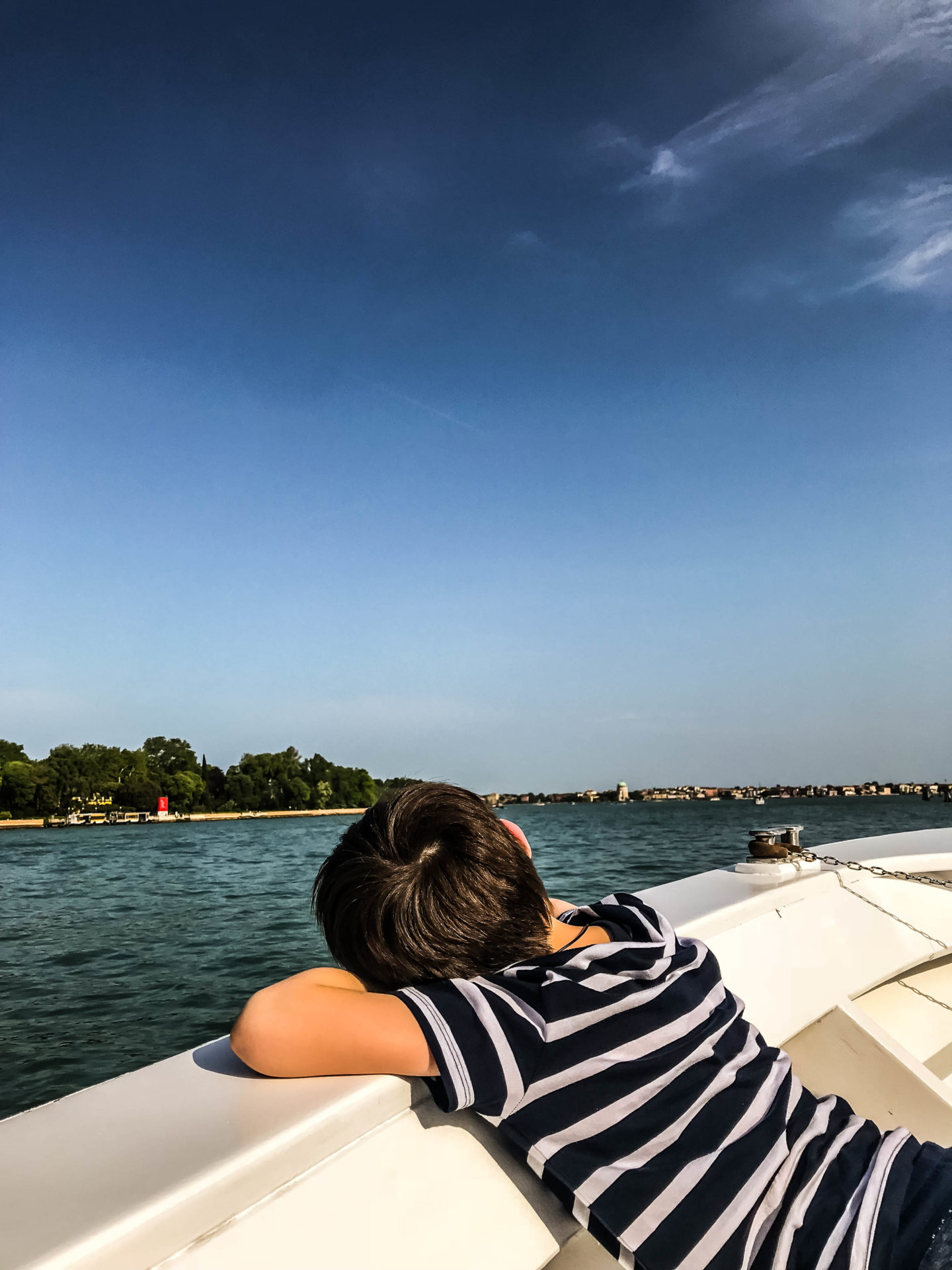 My son relaxing on the boat ride back from Venice