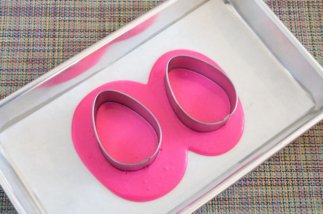 Egg-shaped cookie cutters set into the melted pink coating chocolate | Erin Gardner | Erin Bakes