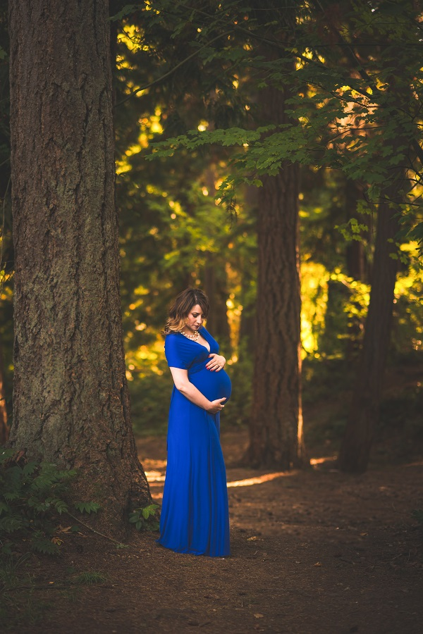 pregnant woman posing for maternity photo in royal blue floor length gown